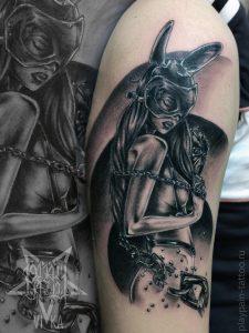 Девушка в маске и в цепях татуировка на плече