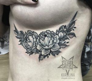 Женская тату на ребрах, цветы в графике с элементами дотворка
